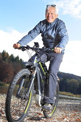 Senior auf E Mountainbike neben Fluss