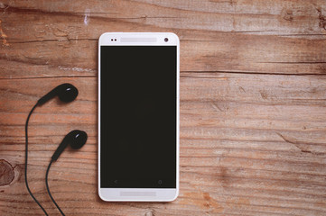 Smart Phone and earphones on wooden table, blank space