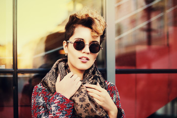 Fashion portrait of young beautiful stilish woman with round sunglasses. Bob short hair. Model looking at camera. City lifestyle. Street fashion concept. Copy space.Toned