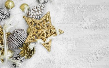 Golden Shiny Christmas Decorations in the Snow with Elegant Ribb