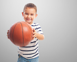 portrait of a little boy holding a basket ball