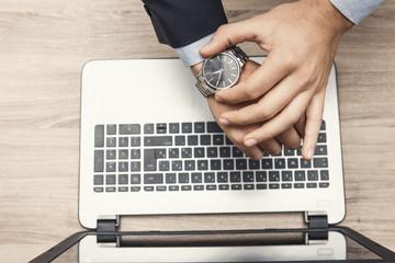 mano di uomo in ufficio con orologio al poloso e tastiera di notebook