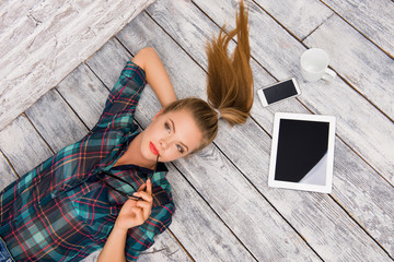 Concentrated girl with tablet, spectacles, phone and cup lying o