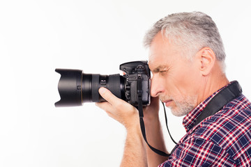 Side view of aged photographer making a photo
