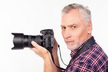 Side view of aged photographer holding a camera