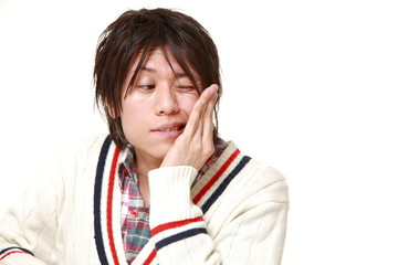 young Japanese man suffers from toothache