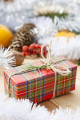 Christmas gift box with New Year's and Christmas decoration midst fruits and tinsel.