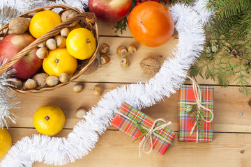 Christmas gift box with New Year's and Christmas decoration midst fruits and tinsel
