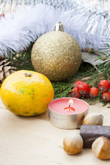 Christmas red candle on wooden table among Christmas and New Year ball and decor