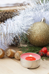 New Year and Christmas red candle on wooden table among Christmas and New Year ball and decor