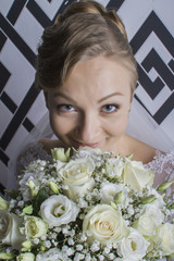 portrait of the beautiful happy bride in wedding day in a bright interior