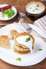 Fried potato pancakes with oatmeal and basil on a white ceramic plate.