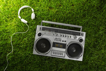 Retro-styled silver boom box and earphones over green grass stud