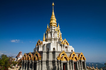 Golden pagoda with blue sky in the north of Thailand.