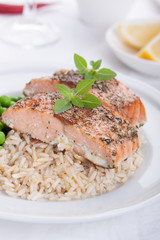 Baked salmon with rice, green peas and basil on a white ceramic plate on a white background.