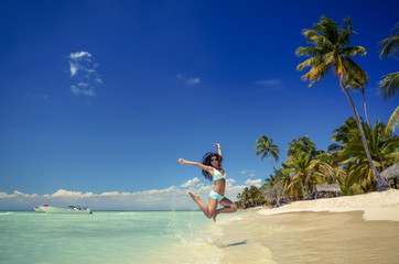 Beautiful tropical beach. Carefree young woman is jumping into the sky.