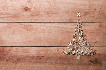 Simple Christmas tree arranged from sawdust, wood-chips on wooden background.