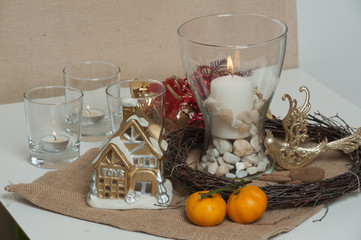 On the table are a candle, a small New Year's house. Christmas