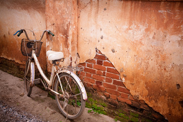 Old bike parked beside the vintage old house.