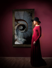 Woman's portrait against the picture with spiral stairs hanging on a wall