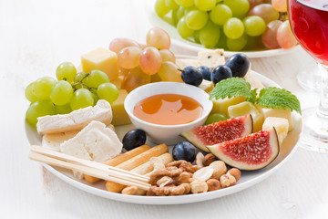 cheeses, fruits, wine and snacks, closeup