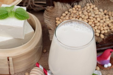 Soy milk and soybeans on wood background.