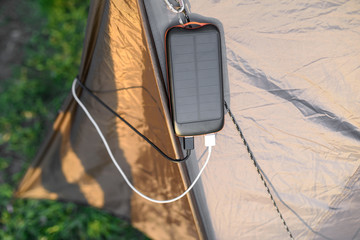 Portable solar panel for charging mobile devices hanging on the tent
