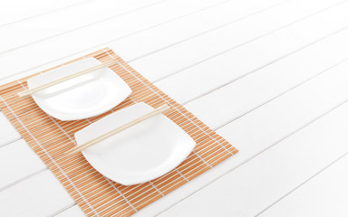 Empty ceramic dish and chopsticks on a wooden plate
