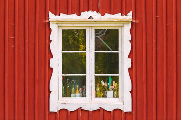 Ancient white window in a red wooden Swedish house