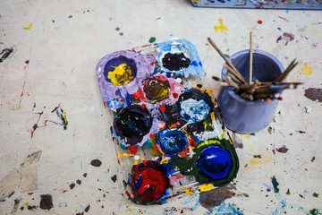 Paints and brushes on table