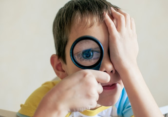 big blue eyes through a magnifying glass. handsome boy playing with a magnifying glass bringing it to the eyes