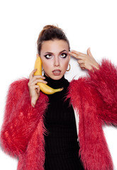 Woman holding a banana as telephone and having fun