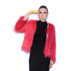 woman wearing pink fur coat making fun with banana