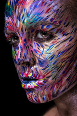 Beautiful fashion woman with bright color face art and body art. Painted lines on face. Creative portrait