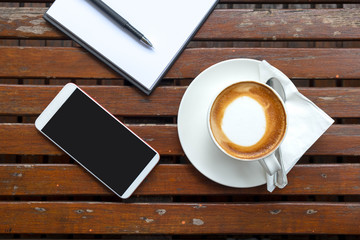 cup of coffee with white paper and smartphone put on wooden table