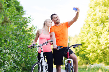 couple with bicycle taking selfie by smartphone