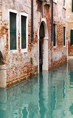 The reflection of a colorful houses in water canal, Venice. Land