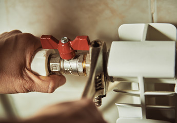 Close-up of mature mechanic hands repairing heating system.