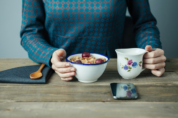 young woman pouring milk into cereal for breakfast on wooden table