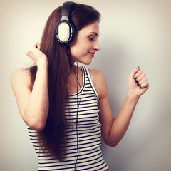 Young beautiful woman listening the music from modern headphones