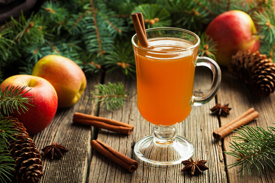 Hot apple cider traditional winter season drink with cinnamon and anise. Homemade healthy organic warm spice beverage. Christmas or thanksgiving holiday decoration on vintage wooden background
