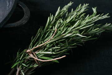 Rosemary on a black wooden background close-up