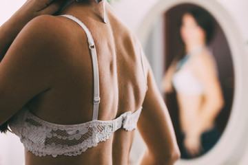 Woman in a white bra, in front of the mirror