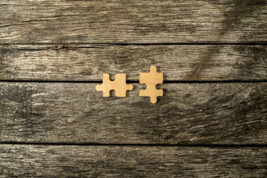 Two blank matching wooden puzzle pieces