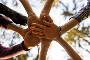 Shot from below of four people stacking hands outside in nature