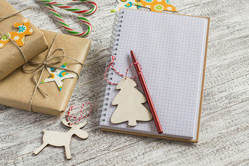Blank open Notepad, Christmas gifts, candies on a light wooden surface