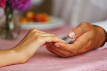 Handsome man holds woman's hand in the restaurant