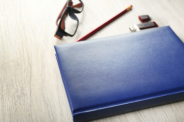 Workplace - blue notebook and stationery on grey wooden background
