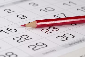 Red pencil over calendar