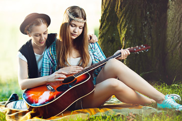 Girls playing guitar in the park
